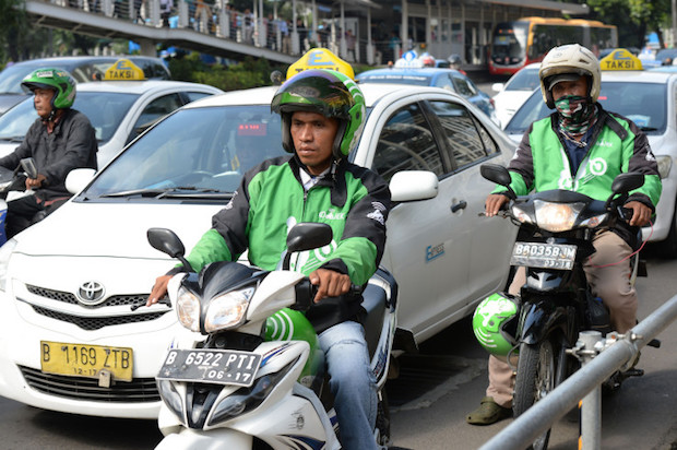 Go-Jek Indonesia Pt. motorcycle taxi riders drive along a street in Jakarta, Indonesia on Monday, March 21, 2016. The Jakarta-based startup has already become a household name in its home country. The startup's app has been downloaded more than 11 million times and it has more than 200,000 motorbikes. Its name is a play on ojek, the Indonesian word for the motorcycle taxis that crisscross Southeast Asia's most populous nation. Photographer: Dimas Ardian/Bloomberg