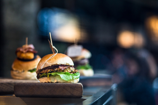 Close up image of a freshly flame grilled burger inside a bun, wilth lettuce, red onion, melted cheese and tomato. There are a few more burgers defocused in the background. The burger rests on a wooden board and the background is pleasantly defocused, leaving plenty of room for copy space. Horizontal colour image processed from an original RAW file,