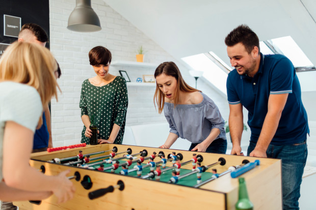 Friends playing foosball at home party. They are enjoying spending time together. One young woman drinking beer from green glass bottle.