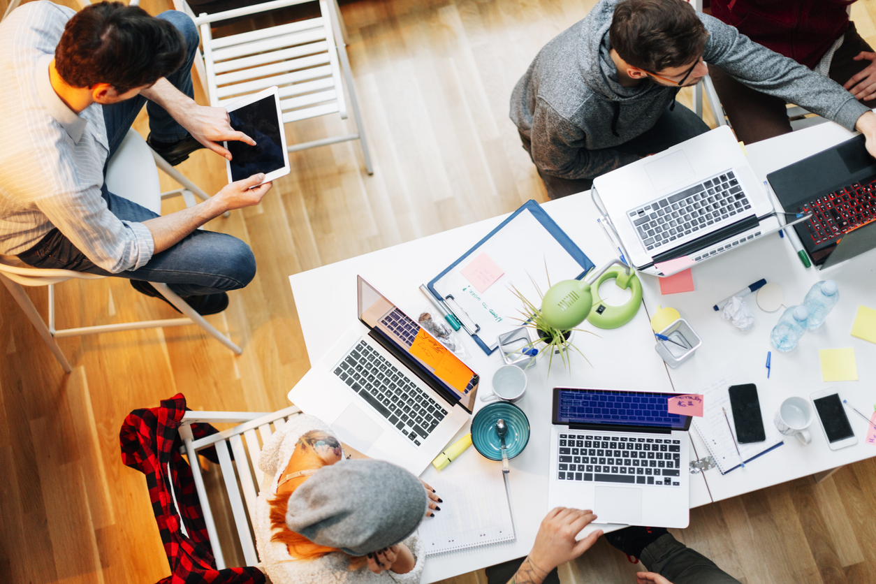 Young developers working in their start-up home office. They are brainstorming, woman holding pencil and writing while talking with her coworker. They are collaborating. Top view. Location is released.