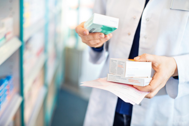 Closeup of pharmacist's hands taking medicines from shelf at the pharmacy