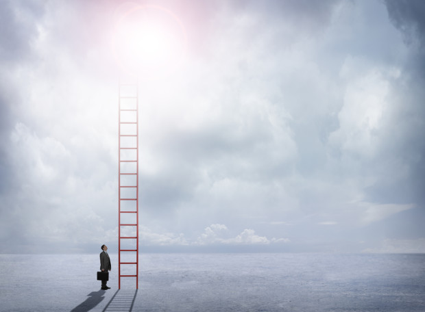 A businessman carrying a briefcase stands at the bottom of a red ladder.  He gazes up at the red ladder which disappears into the cloudy sky.  The clouds allow for text and copy.