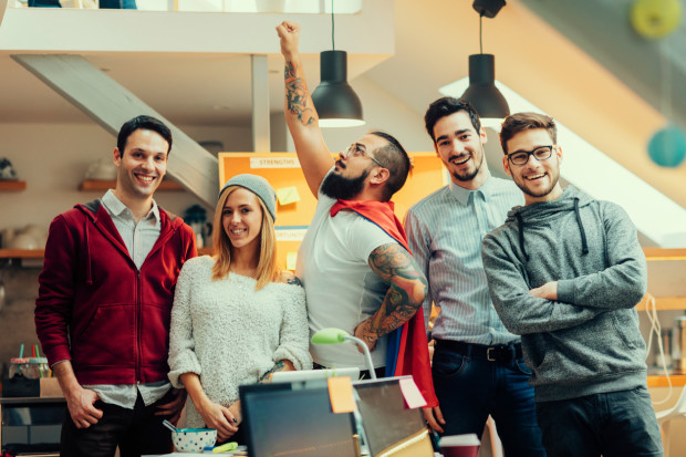 Five young people running their developers startup company. Working in the house like business incubator. Standing and posing for group portrait in their office. Looking at camera and smiling. One of the founders wearing super hero cape and holding his arm raised. Shot with Canon EOS 5Ds.