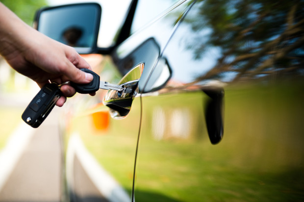 Woman putting key in car door.