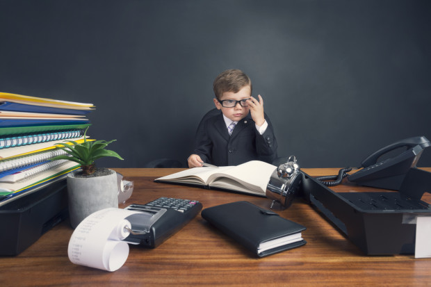 Young boy dressed in a suit working at a large desk. The desk has a calculator, Filofax, phone and clock. He is very busy and there is a lot of work on his desk. He is wearing glasses and looks like an accountant.