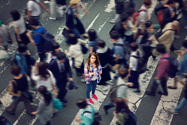 Young caucasian girl is angry because she is lost in the crowd.