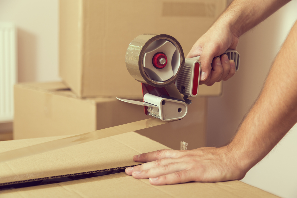 Close up of a guy's hands holding packing machine and sealing cardboard boxes with duct tape