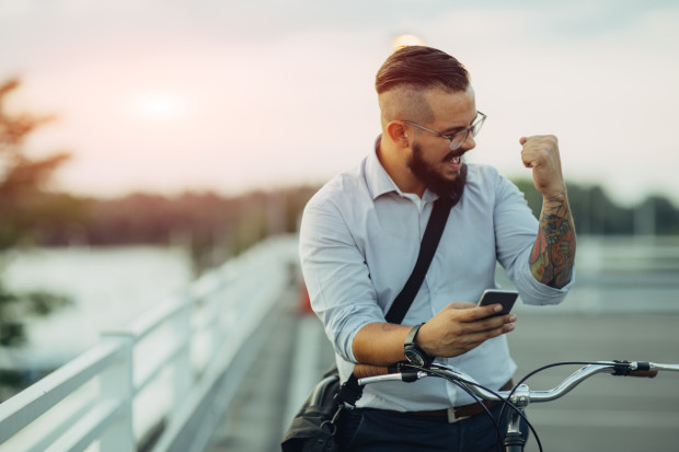 Young Businessman pushing his city bicycle and using his smart phone. He has tattoos and hipster haircut. He just got positive reports from stock market. Using app on his smart phone. He is celebrating his success with fist up.
