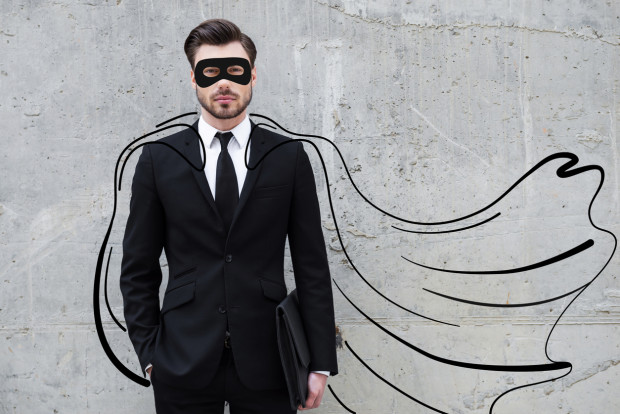 Confident young businessman wearing a drawn cape and mask while standing against concrete wall