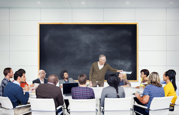 A gray haired man stands in front of a large blackboard and addresses a multiethnic group of students.  The students are sitting around a large table.