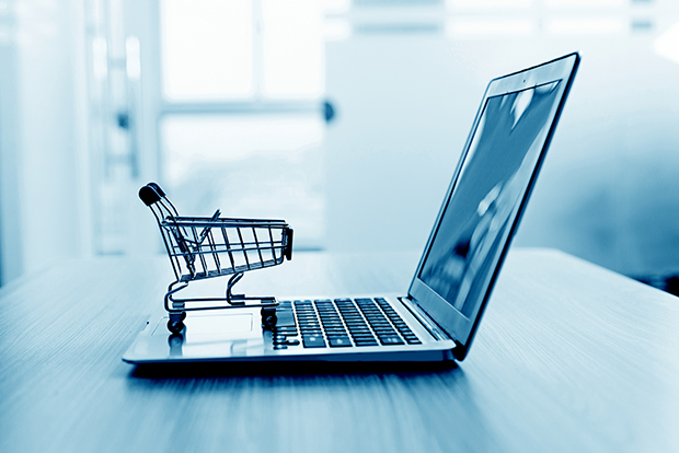 Empty miniature shopping cart on laptop, online shopping concept.