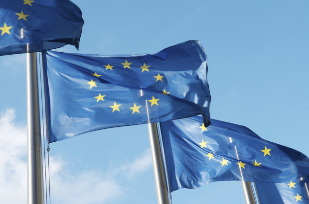 Four European Union flags waving in the wind